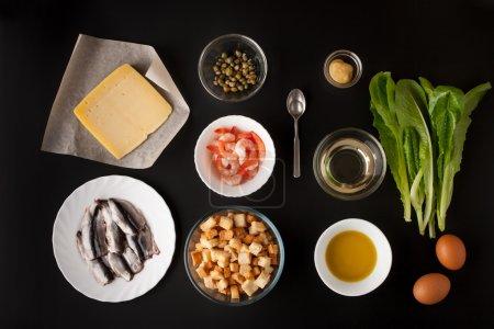 Ingredients for Caesar salad on the black background horizontal