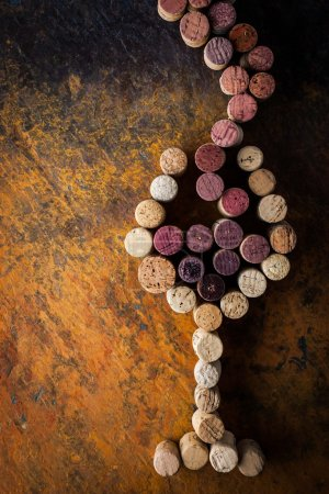 Glass of wine nade by corks on the colorful background