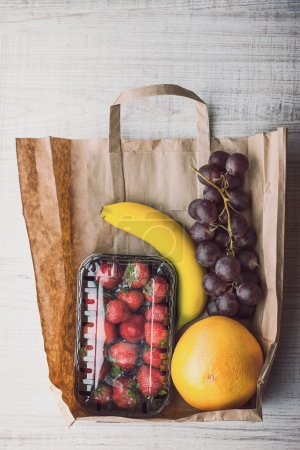 Strawberry with different fruit inside a paper bag vertical