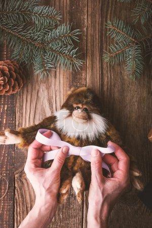 Photo pour Attacher le ruban violet sur un jouet de singe sur la table en bois vertical - image libre de droit