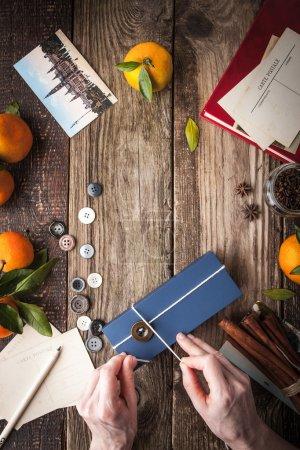 Photo pour Emballage cadeau avec mandarines, button, cartes postales, anis étoilé, clous de girofle et la cannelle sur la table en bois verticale - image libre de droit