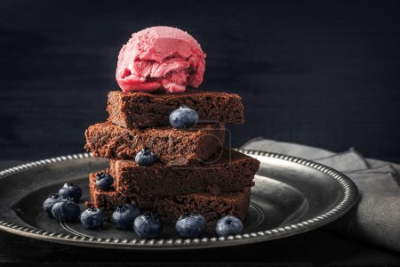 Photo for Chocolate brownie with blueberry  and ice cream on the vintage plate on the black wooden table horizontal - Royalty Free Image