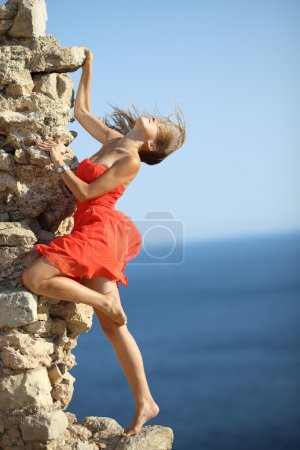 Photo for Beautiful girl in red dress posing on the coast - Royalty Free Image