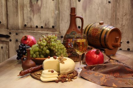 white wine, cheese, nuts, grapes and pomegranate