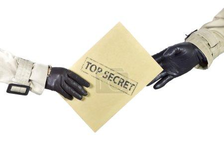 Photo pour Deux personnes avec de la gabardine et des gants bruns échangeant des documents privés . - image libre de droit