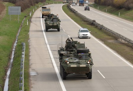Strykers,wheeled armored vehicles drive on highway .