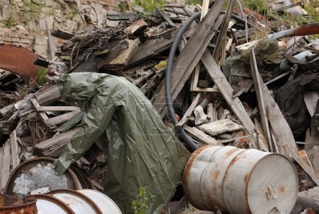 Man with gas mask and green military clothes  explores barrels after chemical disaster.