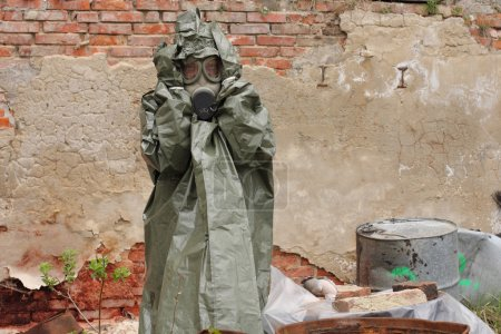Man with gas mask and green military clothes  after chemical disaster.