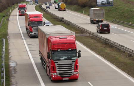 Three red trucks  on highway