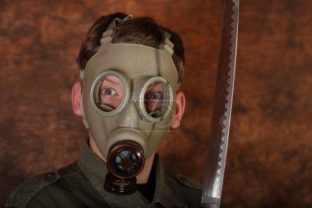 Man with gas mask and  katana sword on brown batik  background