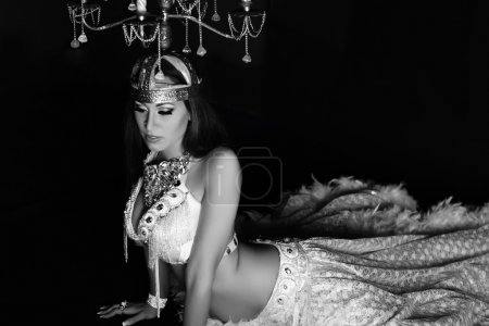 Beautiful woman in white stage arabic belly dance costume, candelabrum with candles on head
