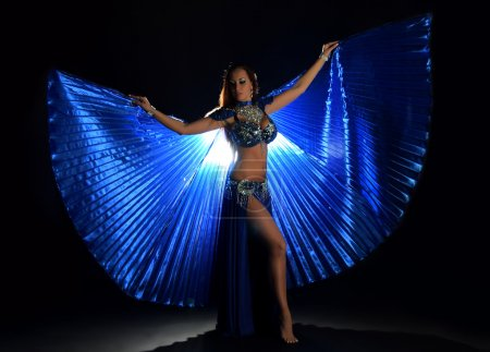 Belly dancer woman in blue costume with wings on dark background