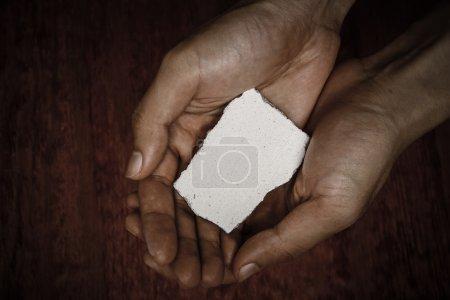 Photo pour Bloc de pierre vierge dans les mains avec fond sombre . - image libre de droit