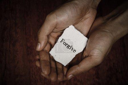 Photo pour Pardonner bloc de pierre dans les mains avec fond sombre . - image libre de droit