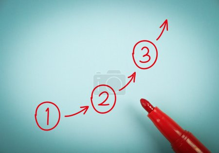 Photo for Step by step concept is on blue paper with a red marker aside. - Royalty Free Image