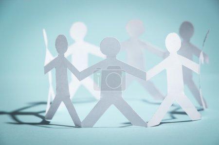 Photo pour Un groupe de gens en papier se tiennent la main. Concept d'équipe . - image libre de droit