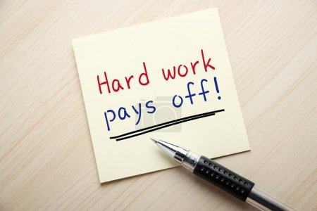 Photo for Text Hard Work Pays Off is written on the sticky note with ball pen aside. - Royalty Free Image