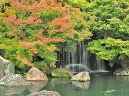 waterfall and red leaves in autumn season at Koko-en garden, Himeji, Japan.