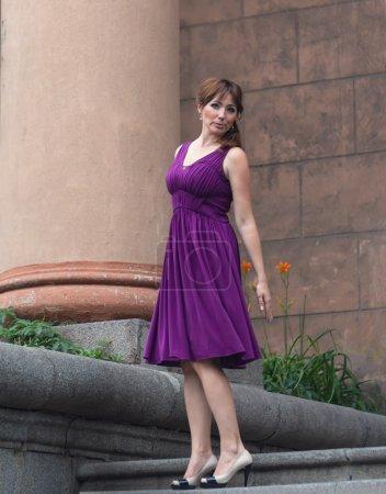 Beautiful woman in purple dress near the column. People
