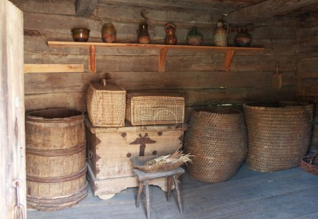 Chests, barrels and a shelf with dishes in the ancient peasant hut