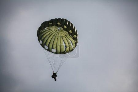 Parachutist in cloudy sky