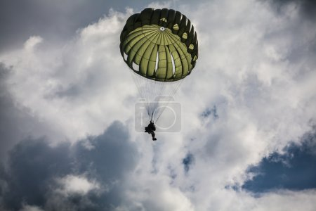 Parachutist in cloudy sky