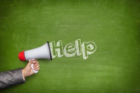 Photo for Help text on blackboard and Businessman hand holding megaphone on front of vintage full frame black blank blackboard no frame - Royalty Free Image