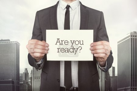 Photo for Are you ready on paper what businessman is holding on cityscape background - Royalty Free Image