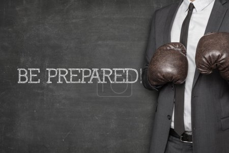 Photo for Be prepared on blackboard with businessman wearing boxing gloves - Royalty Free Image