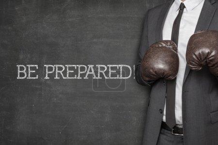 Photo pour Être préparées sur tableau noir avec l'homme d'affaires avec des gants de boxe - image libre de droit