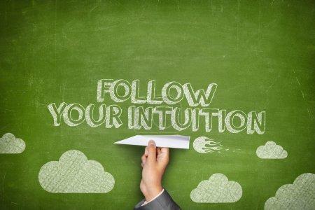 Photo pour Suivez votre concept d'intuition sur tableau noir vert avec main d'affaires avion en papier - image libre de droit