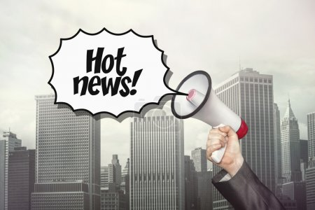 Photo pour Hot news texte sur bulle de discours avec mégaphone que l'homme d'affaires tient sur fond de paysage urbain - image libre de droit