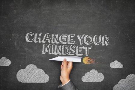 Photo pour Changez votre concept d'état d'esprit sur le tableau noir avec l'homme d'affaires main tenant avion en papier - image libre de droit