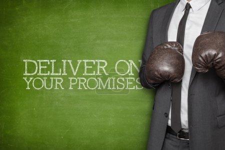 Photo pour Tenir vos promesses sur tableau noir avec l'homme d'affaires avec des gants de boxe - image libre de droit