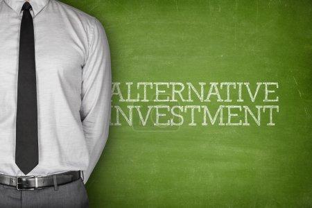Photo pour Texte d'investissement alternatif sur tableau noir avec l'homme d'affaires de côté - image libre de droit