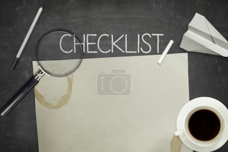 Checklist concept on black blackboard with empty paper sheet