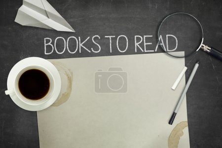 Books to read concept on black blackboard with empty paper sheet