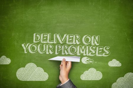 Photo for Deliver your promises concept on green blackboard with businessman hand holding paper plane - Royalty Free Image