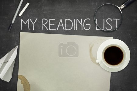 My reading list concept on black blackboard with empty paper sheet