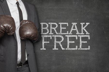Photo for Break free on blackboard with businessman wearing boxing gloves - Royalty Free Image