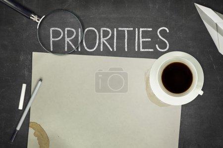 Priorities concept on black blackboard with empty ...