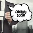 Coming soon text on speech bubble with businessman...