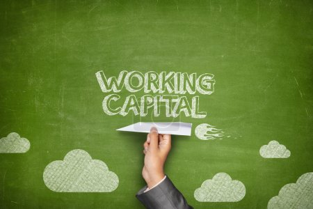 Photo pour Working capital concept on green blackboard with businessman hand holding paper plane - image libre de droit