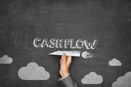 Photo for Cash flow concept on black blackboard with businessman hand holding paper plane - Royalty Free Image