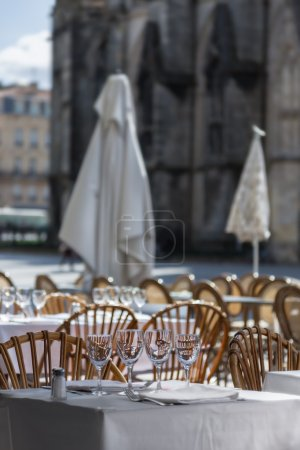 Tables outdoor cafes with wine glasses on the square of the Fren