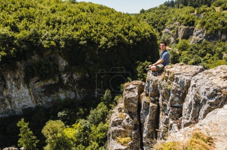 Photo for Young man sitting on the edge of a cliff smiling and overlooking a forested valley in summer - Royalty Free Image