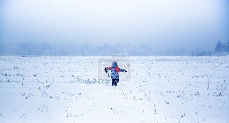 Little girl running away in a snowy park