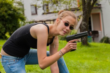 Teenage girl with gun at the ready