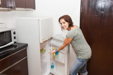 A woman shows with her hand in an empty fridge