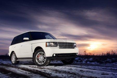 Photo pour Voiture premium blanche rester sur la route de neige au coucher du soleil - image libre de droit